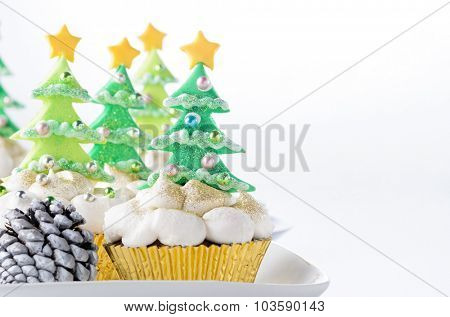 Christmas tree cupcakes with butter cream icing as snow on white background