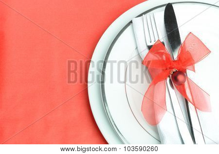 Christmas dinner cutlery tied with organza red ribbon and holiday bauble on white silver lined plates