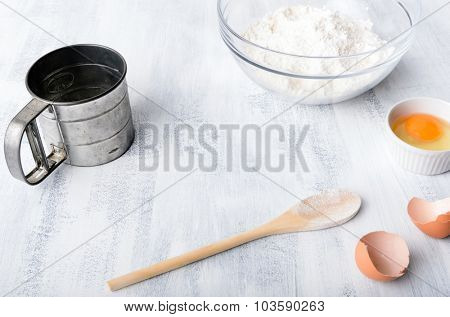 Flour, eggs and baking tools on a board with copy space in the middle