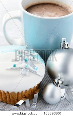 Silver and blue theme christmas; snowy frosty icy cupcake with xmas tree motif with baubles, ribbons and mug of hot chocolate