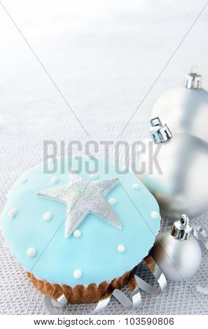 Silver christmas baubles and ribbons with cool blue tone cupcake and a large star