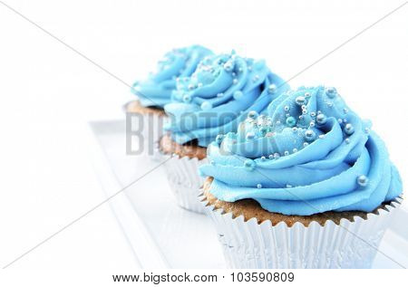 Delicious cupcakes with blue frosting and decorative sprinkles on a plate