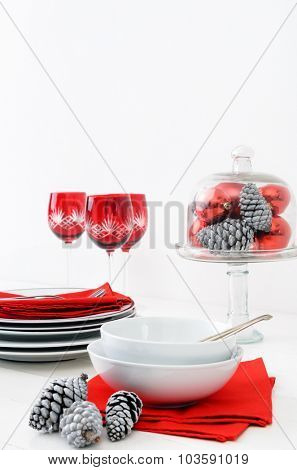 Casual christmas table setting crockery display in red and white theme, pine cones, xmas baubles decorations