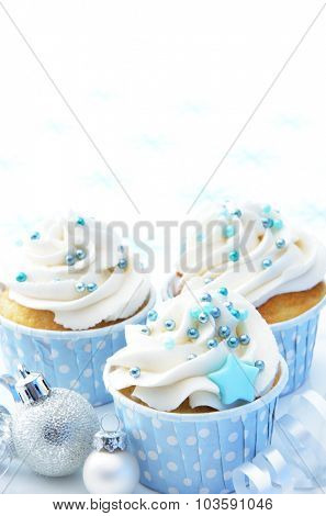 Cupcakes with winter theme, ribbons and silver christmas baubles. plenty of copy space