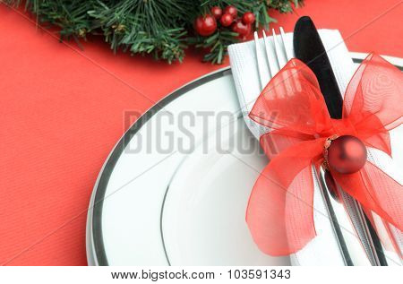 Christmas place setting with red ribbon and bauble