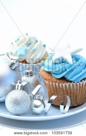Blue and white icing frosted cupcakes with silver christmas decoration baubles and ribbons on a plate