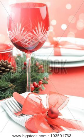 Christmas table setting and festive seasonal lighting bokeh in traditional red and white with plates, cutlery, wine glasses