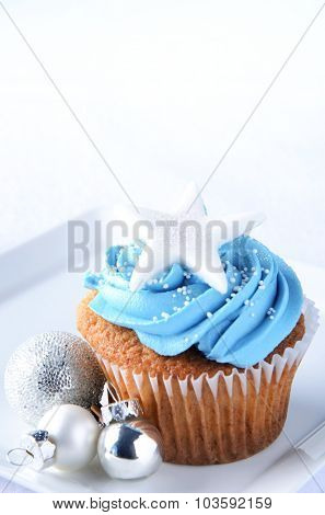 Winter frosty cupcakes with blue icing with star and christmas decorations