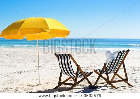 Beach chairs and yellow umbrella in sand with bright sunlight