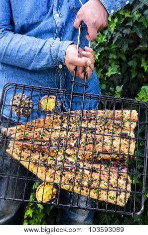 Home chef showing his perfectly grilled fish fillet basted in lemon and herb butter at a barbeque barbecue bbq