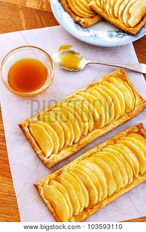 Appetizing glazed apple confectionary, on baking paper and a wood background