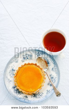 Delicious creme brulee dessert served on vintage crockery and a cup of tea, lots of copyspace
