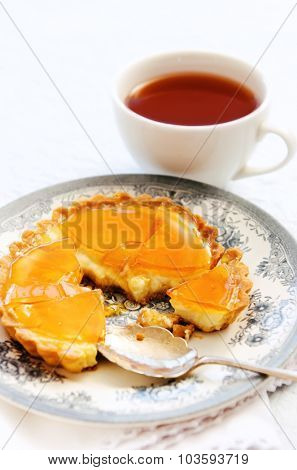 Unfinished custard tart with a caramelised surface served with a cup of black tea