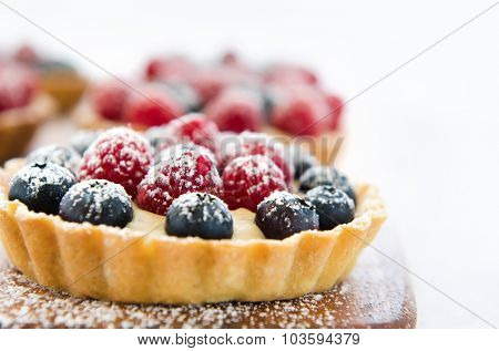 Appetizing close up of a fruit tart consisting of blueberries and raspberries, sprinkled with icing sugar