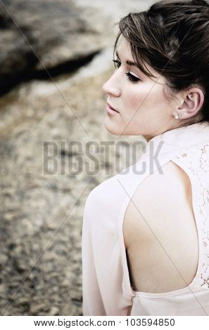 Elegant side  and back profile of a young woman sitting on a boulder