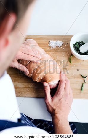 Chef hands rubbing salt spices into a pork shoulder, preparing seasoning a roast