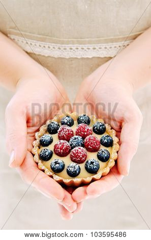 Woman in apron holds a fruit dessert, her hands forming a heart shape