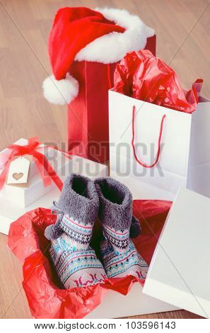 Christmas shopping bags with santa's hat and gift boxes, open present of woollen woven boots for winter on wooden floor