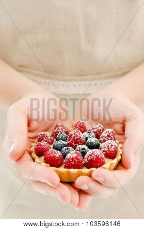 Woman in apron cradling a fresh gourmet tart, her hands forming a heart shape