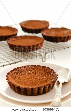 Focus on a dark chocolate dessert tart served on a plate with more in the background