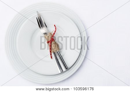 Holiday table setting with cutlery tied in hessian and red ribbon on white table cloth