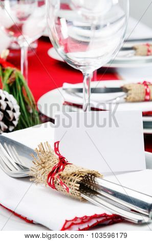 Christmas holiday dinner setting in red and white theme with empty place card, copy space