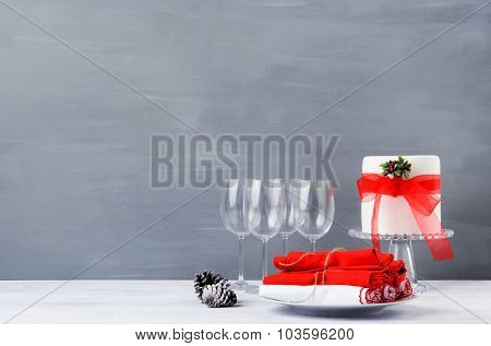 Modern minimalist christmas decoration with crockery, wine glasses and beautifully decorated cake on dark grey background