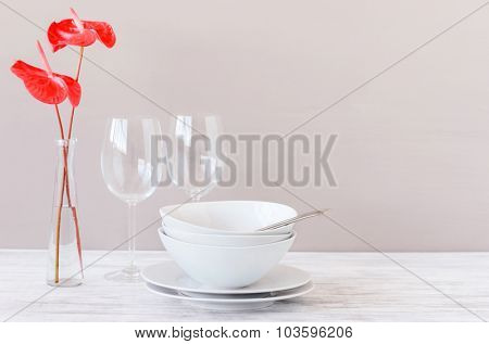 Simple modern minimalistic table setting with wine glasses, white crockery and red flowers