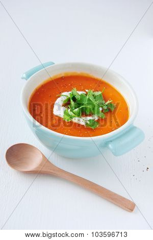 Roasted sweet potato tomato soup with coconut milk cream and coriander garnish, healthy meal on white background