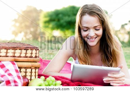Happy carefree smiling summer girl looking at her tablet computer, staying connected, wireless technology in outdoor park