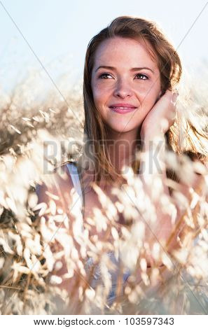 Beautiful happy carefree young girl sits in field of golden weeds and poses for a portrait