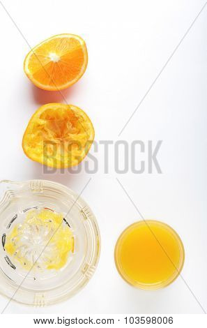 Glass Juicer with cut oranges on white background, overhead perspective