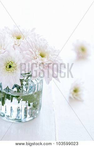 Close up of a small arrangement of white flowers in a clear vase