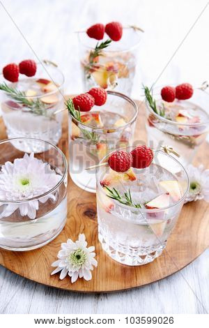 Fruity cocktails/soda water being served on a wooden tray decorated with flowers, raspberries, sliced apples and garnish