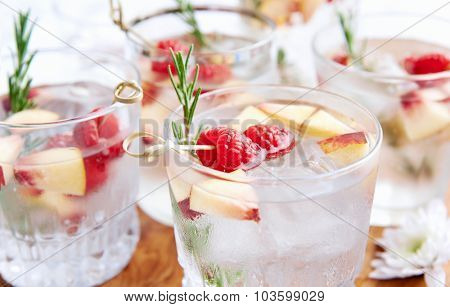 Close up of clear cocktails/soda water being served on a wooden tray decorated with flowers, raspberries, sliced nectarine and rosemary garnish