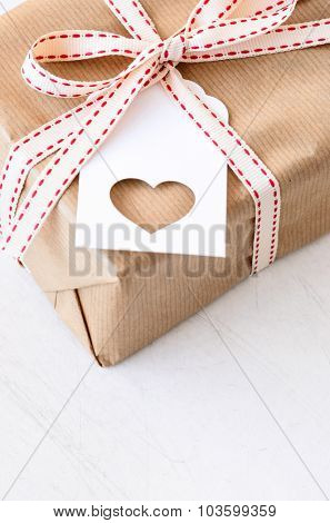 Present box tied with bow with heart gift tag, birthday christmas valentines day special occasion