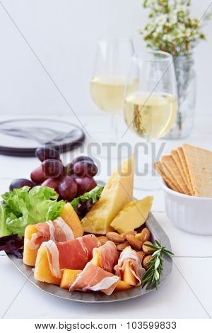 Platter of gourmet party food, gruyere cheddar cheese with prosciutto parma ham wrapped rockmelon served with white wine