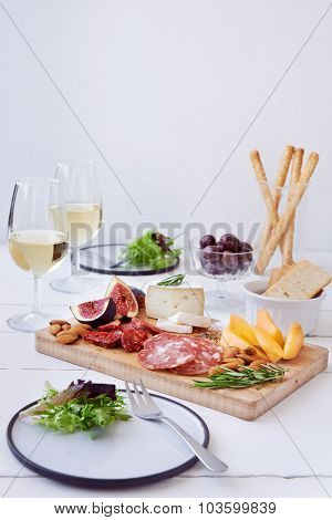 Cheese and charcuterie pairing, chorizo salami, served with fresh fruit rockmelon, fig with olives, salad and white wine