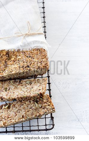 Healthy seeded multi grain whole wheat wholemeal loaf of bread with nuts, pumpkin, sunflower, sesame, flax seeds and almonds, plenty of copy space