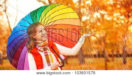 Happy Woman With Rainbow Multicolored Umbrella Under Rain In Park