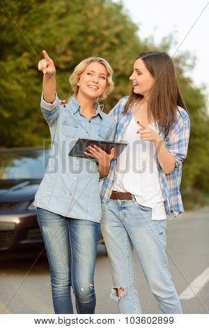 Positive girls holding laptop
