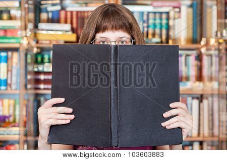 Girl Reads Big Book In Library