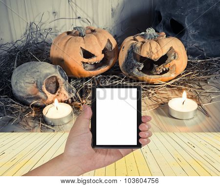 Male Hand Is Holding A Modern Touch Screen Phone And Rotten Halloween Pumpkin With Candle Light .