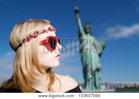 Cute girl in hipster sunglasses on New York background