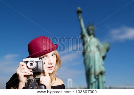 Girl in hipster glasses with camera on New York background