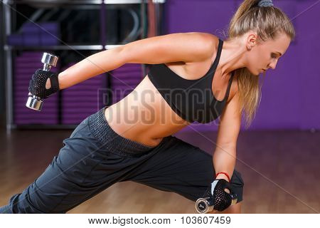 Side view of fitness woman wearing in black top and breeches doing exercises with dumbbells on the sport equipment background in the gym waist up