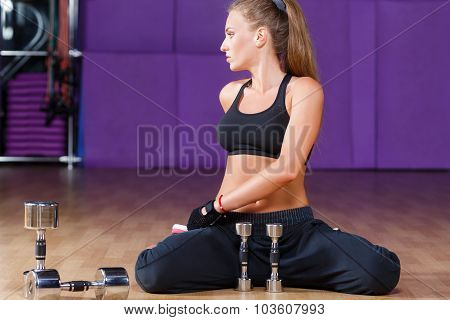 Athletic woman wearing in black top and breeches sitting on the floor with dumbbells on the sport equipment background in the gym full body