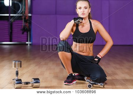 Young fitness woman wearing in black top and breeches posing on the floor with dumbbells on the sport equipment background in the gym full body