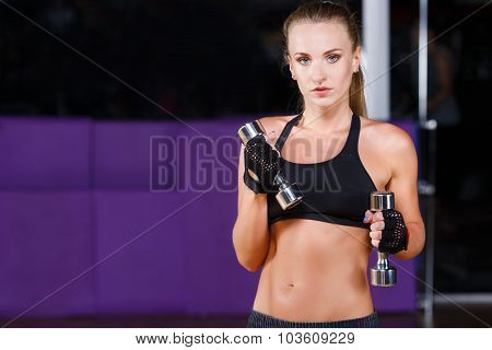 Serious fitness woman wearing in black top and breeches posing with dumbbells and looking at camera on the sport equipment background in the gym waist up