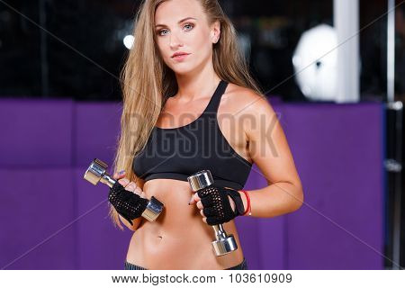 Strong young woman with long hair wearing in black top and breeches holding dumbbells and looking at camera on the sport equipment background in the gym waist up